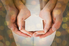 Composite image of couple holding miniature house in hands Royalty Free Stock Image