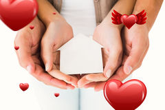 Composite image of couple holding miniature house in hands Stock Images