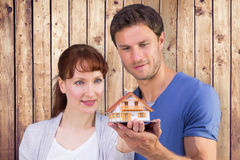 Composite image of couple holding a model house Royalty Free Stock Image