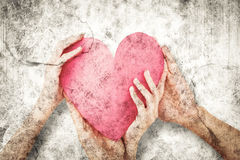 Composite image of couple holding a paper heart Royalty Free Stock Images