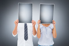 Composite image of couple holding paper over their faces Stock Photography