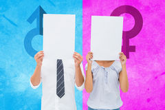 Composite image of couple holding paper over their faces Stock Images