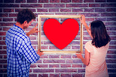 Composite image of couple holding picture frame Stock Photo