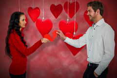Composite image of couple holding red cracked heart shape 3d Royalty Free Stock Photos
