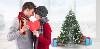 Composite image of couple holding a red heart Stock Image