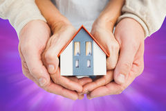 Composite image of couple holding small model house in hands. Couple holding small model house in hands against purple abstract light spot design Stock Images
