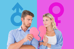 Composite image of couple holding two halves of broken heart Royalty Free Stock Photo