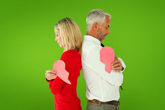 Composite image of couple holding two halves of broken heart Stock Photography