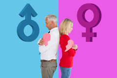 Composite image of couple holding two halves of broken heart Royalty Free Stock Photography