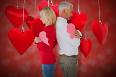 Composite image of couple holding two halves of broken heart 3d. Couple holding two halves of broken heart against valentines heart design 3d Stock Image
