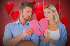 Composite image of couple holding two halves of broken heart 3d. Couple holding two halves of broken heart against valentines heart design 3d Royalty Free Stock Photography