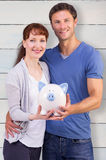 Composite image of couple holding a white piggy bank Stock Photo