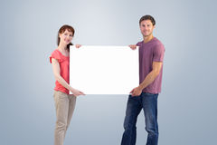 Composite image of couple holding a white sign Royalty Free Stock Photography
