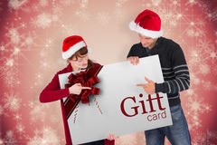 Composite image of couple holding a white sign Stock Images