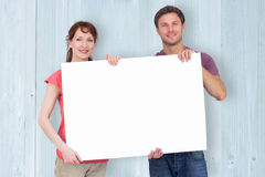 Composite image of couple holding a white sign Stock Photo