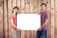 Composite image of couple holding a white sign Royalty Free Stock Image