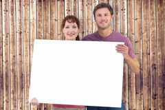Composite image of couple holding a white sign Stock Photography