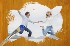 Composite image of couple jumping on the beach Stock Photography