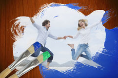 Composite image of couple jumping on the beach Royalty Free Stock Photography