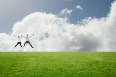 Composite image of couple jumping and holding hands Royalty Free Stock Images
