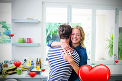 Composite image of couple in kitchen and valentines heart 3d. Hearts against couple hugging in kitchen 3D Royalty Free Stock Photo