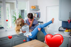 Composite image of couple in kitchen and valentines hearts 3d. Hearts against handsome man carrying wife 3D Royalty Free Stock Photos