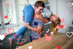 Composite image of couple laughing and valentines hearts 3d. Valentines heart design against handsome man carrying wife 3d Royalty Free Stock Photos