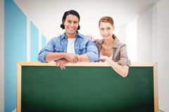 Composite image of couple leaning on blank wall Royalty Free Stock Photos