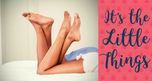 Composite image of couple legs on bed and valentines words Royalty Free Stock Photography