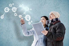 Composite image of couple looking away while holding digital tablet. Couple looking away while holding digital tablet against blue background Stock Photos