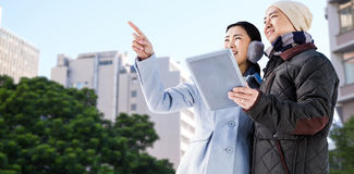 Composite image of couple looking away while holding digital tablet. Couple looking away while holding digital tablet against low angle view of city buildings Stock Photography