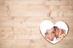 Composite image of couple looking through torn paper Royalty Free Stock Photography