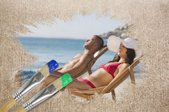 Composite image of couple lying on the beach Royalty Free Stock Photo