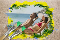 Composite image of couple lying on the beach Stock Photos