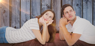 Composite image of couple lying on floor and looking up Royalty Free Stock Photos