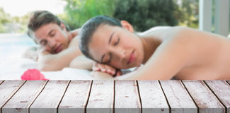 Composite image of couple lying on massage table at spa center Royalty Free Stock Photo