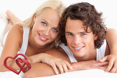 Composite image of couple lying on their bed Royalty Free Stock Photos