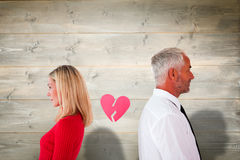 Composite image of couple not talking with broken heart between them Stock Photography
