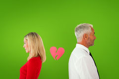 Composite image of couple not talking with broken heart between them Stock Image