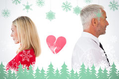 Composite image of couple not talking with broken heart between them Stock Images