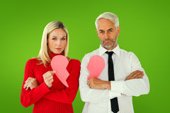 Composite image of couple not talking holding two halves of broken heart Royalty Free Stock Images