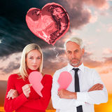 Composite image of couple not talking holding two halves of broken heart Stock Image