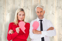 Composite image of couple not talking holding two halves of broken heart Royalty Free Stock Photo