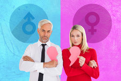 Composite image of couple not talking holding two halves of broken heart Stock Photography