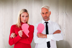 Composite image of couple not talking holding two halves of broken heart Stock Photos