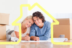 Composite image of couple organizing their future home. Couple organizing their future home against house outline Stock Images