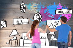 Composite image of couple painting a wall together Royalty Free Stock Photo