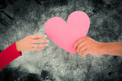 Composite image of couple passing a paper heart Stock Photography