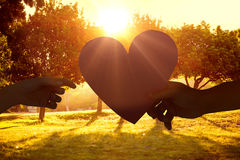 Composite image of couple passing a paper heart Stock Image
