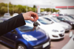 Composite image of couple receiving car keys by a dealer. Couple receiving car keys by a dealer against cars parked at street Royalty Free Stock Photo